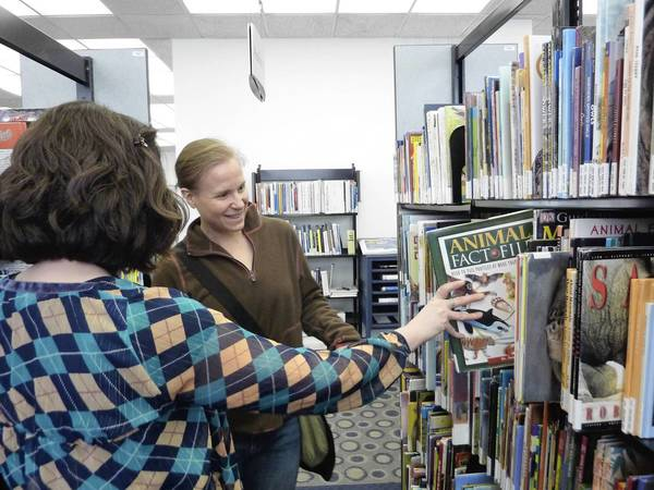 A librarian helps Julie Brame (right) find a book to homeschool her children at Northbrook Public Library, 1201 Cedar Lane, in Northbrook. The library is in a middle of a technology push featuring a 3D printer and advance computer software.