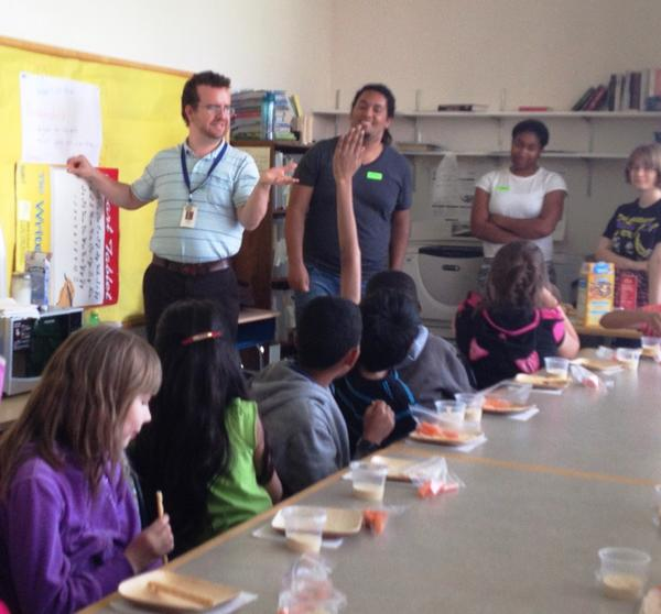 English for Speakers of Other Languages teacher Ryan Cronin asks students what's in hummus. The third through fifth graders had an interactive cooking class with students from Hall High School's global problem solving course.