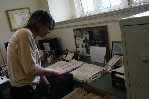 Affordable housing advocate Gail Schechter, executive director of Open Communities, goes through documents at her office on April 25. Schechter and others pushed for the state law that recognizes the importance of affordable housing and encourages municipalities to pass affordable housing plans and to work with developers.