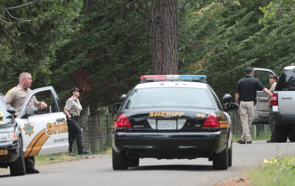 Shasta County Sheriff's deputies investigate the scene of a triple homicide in Shingletown, Calif.
