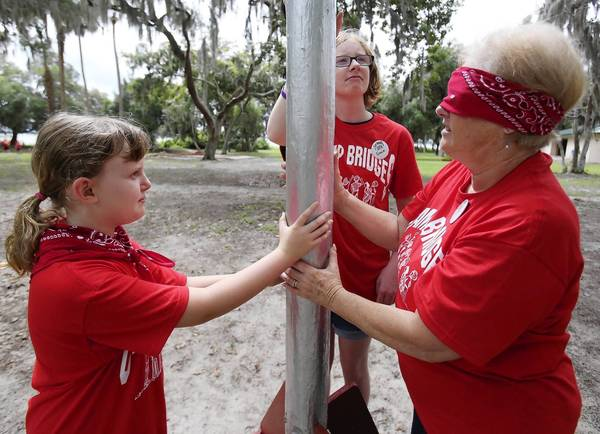 Paris Chambliss, 9, left, and volunteer Susan Meyers, right, participate in a trust building exercise during Cornerstone Hospice and Palliative Care's 19th Annual Camp Bridges May 4 at Warren Willis Camp in Fruitland Park.