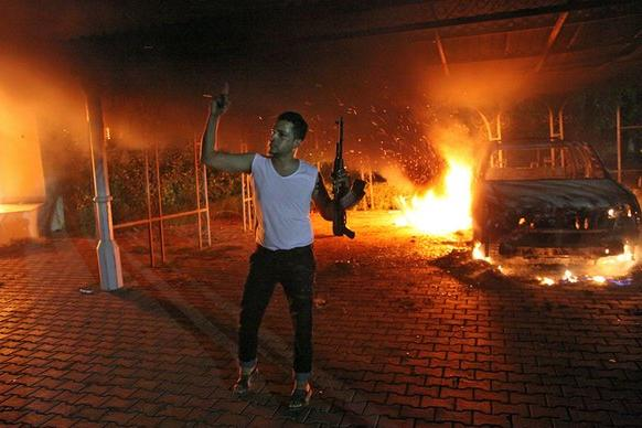 A man waves a rifle as buildings and cars are engulfed in flames inside the U.S. consulate compound in Benghazi, Libya.