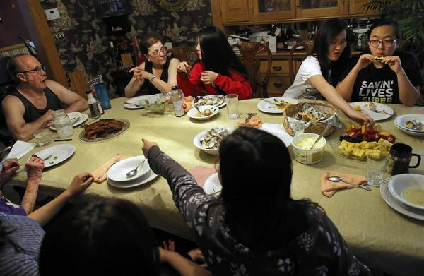 Clockwise, Todd Ochs, Janet Agranoff, Mei Lynn Ochs, 14, Maggie Ochs, 17, and Anna Choi, 17, have dinner together last week in the family's Chicago home. In the foreground are the other children of the household: Lily Ochs, 18, from left, Pim Sunsaneevithayak, 17, and Nora Ochs, 11. At far left is Agranoff's mother, Frances. Todd Ochs and Janet Agranoff, married doctors, adopted Lily, Mei Lynn, Maggie and Nora from China at different times beginning in 1998. Anna Choi is a friend of Lily's who is staying with the family, and Pim Sunsaneevithayak is an exchange student from Thailand.