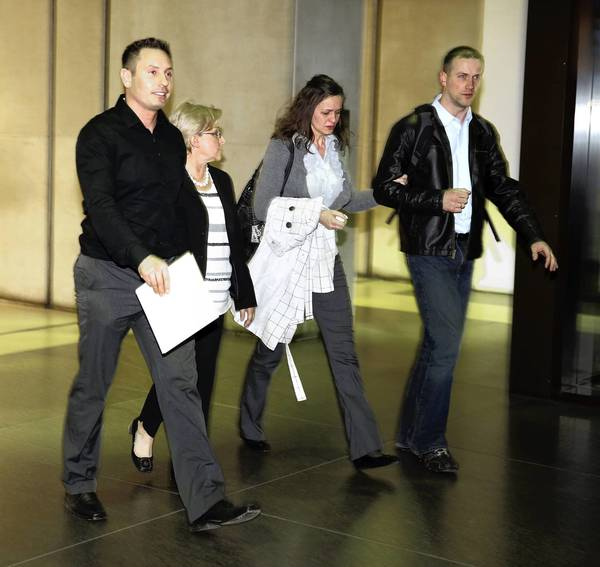 A walks Family members of murder victim Urszula Sakowska, including fiance Grzegorz Magiera, left, are led through the lobby of the Leighton Criminal Court Building by a victim's services representative ,second from left, after a guilty verdict was reached in the trial of Sakowska's accused killer, Anthony Triplett.