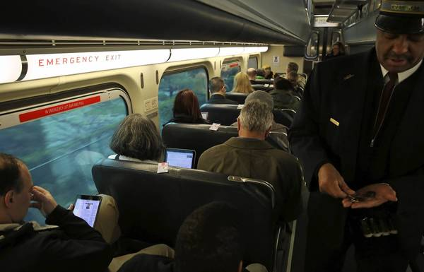 Metra passengers use wireless devices on an inbound train Friday.