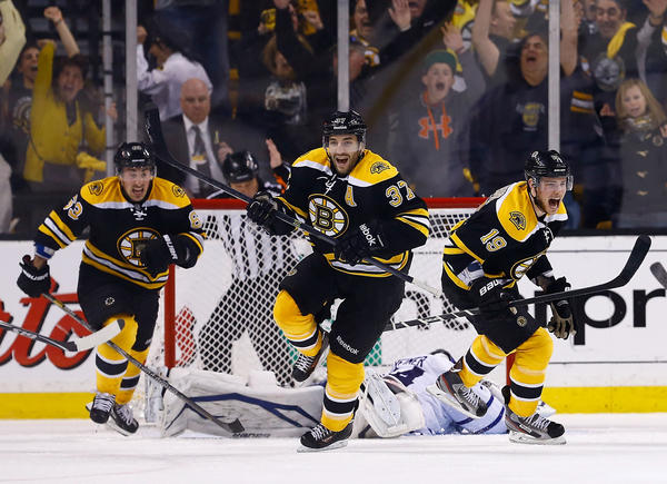 Patrice Bergeron, center, Tyler Seguin, right, and Brad Marchand celebrate after Bergeron's game-winning overtime goal against the Toronto Maple Leafs in Game 7 Monday night in Boston.