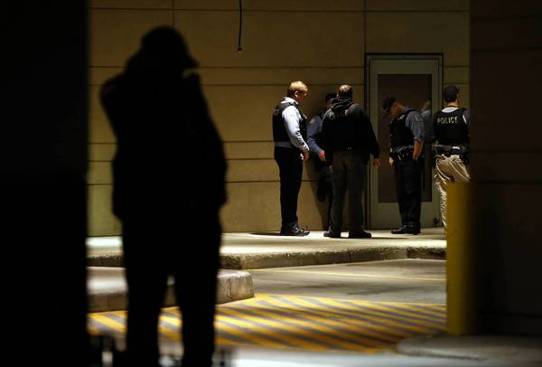 Chicago police officers wait outside the Northwestern Hospital emergency room for news about an injured colleague.