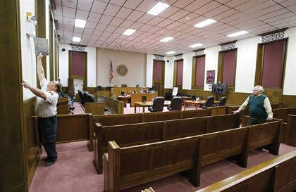 Mike Thompson, fire marshal with Aberdeen Fire and Rescue, left, reaches to test the emergency light in the fourth-floor courtroom as Federal Judge Charles Kornmann, far right, looks on as Thompson performed an inspection of the federal courthouse building Friday.