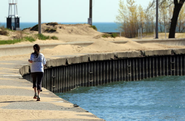 A woman runs along the lakefront path near North Avenue Beach as temperatures begin to climb in the city.
