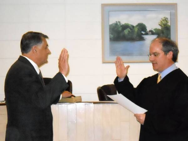 Island Lake Mayor Charles Amrich is sworn in by McHenry County Judge Michael Feetterer at a Thursday board meeting.