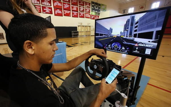 Jonathan Nieves, 18, a Colonial High School student sits in an AT&T driving simulator Tuesday, May 14, 2013, experiencing first-hand the dangers of texting behind the wheel.