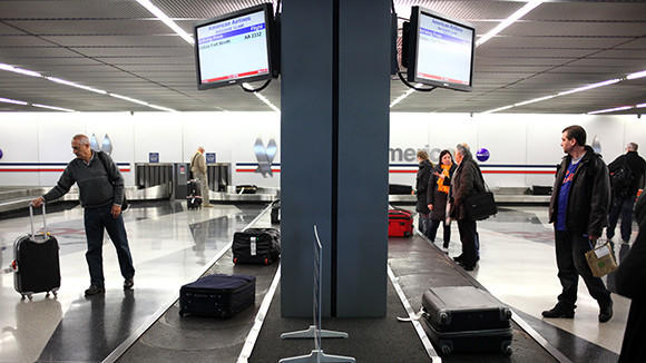 Passengers of an American Airlines flight pick up their luggage at O'Hare International Airport on March 9, 2012.