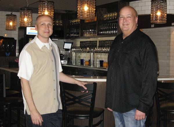 Co-owners Tom Kara and Ed Nemec (in black) in front of the wine taps at their restaurant Dancing Marlin in Franklin.