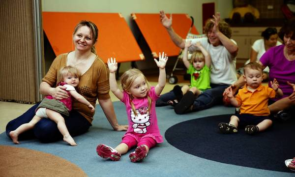 Agnes Niewrzol, left, holds her slumping 11-month-old daughter Weronka, while 2-year-old Amelia reaches skyward during story time in Naperville.