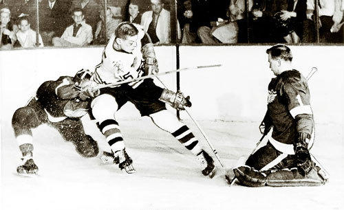 Action from the 1961 Stanley Cup Finals. Eric Nesterenko [15] of the Chicago Blackhawks tries to outmaneuver goalie Hank Bassen [1] of the Detroit Red Wings in the 2nd period of the Stanley Cup playoff game.