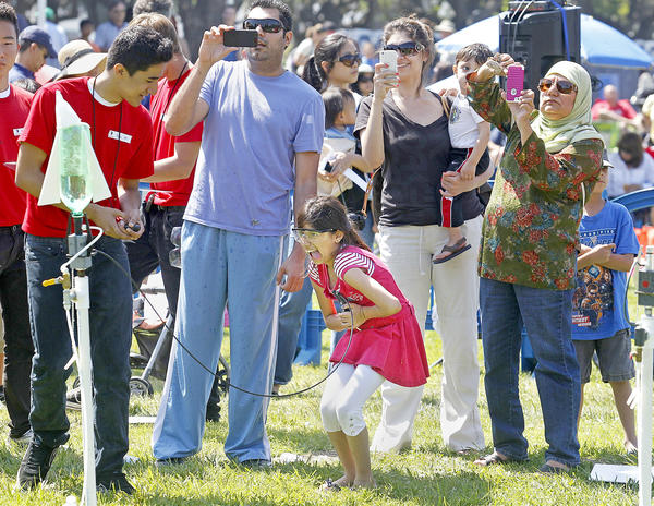 Asiya Umar, 10, bottom center, of Tustin, squeezes down on a trigger to launch her bottle rocket, as her family, from right, grandmother Sheila, mother Laila and father Mohammed look on through their camera phones during Discovery Science Center's annual Rocket Launch event in Huntington Beach on Saturday.