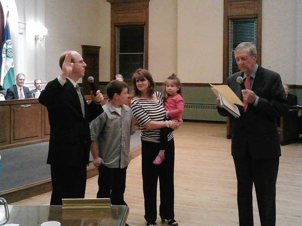 Tom Livingston, left, is sworn in by Village Clerk Thomas Morsch on Monday night. Livingston's family surrounds him.