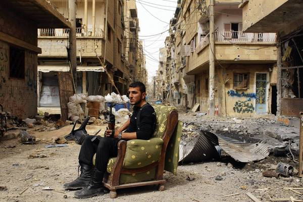 A member of the Free Syrian Army holds his weapon as he sits on a sofa in the middle of a street in Deir al-Zor onApril 2. The United States believes with varying degrees of confidence that Syria's regime has used chemical weapons on a small scale.