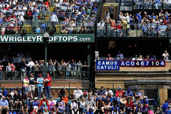 Fans fill the right field bleachers and the rooftops during a Cubs game this month at Wrigley Field. A Tribune/WGN-TV poll shows nearly half of voters favor neither the team nor the rooftop owners in the dispute over the ballpark's renovation.