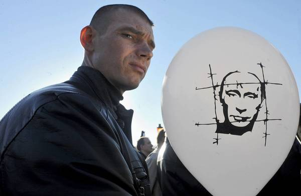 A protester holds a balloon bearing a caricature of Russian President Vladimir Putin during an opposition rally this month in St. Petersburg. A year into Putin's return to the presidency, a crackdown on nongovernmental organizations is in full force.
