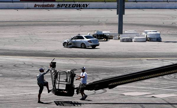 A film crew readies a camera on a boom to film a Mercedes-Benz commercial at Irwindale Speedway.