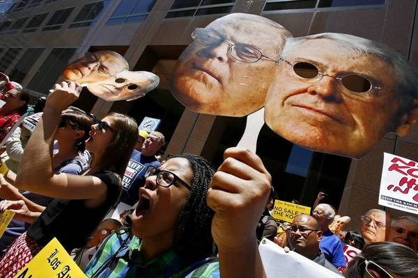 Erinn Carter, right, takes part in a rally organized by the AFL-CIO in front of Oaktree Capital Management's office in Los Angeles to protest the potential sale of the Los Angeles Times to the politically conservative Koch brothers.