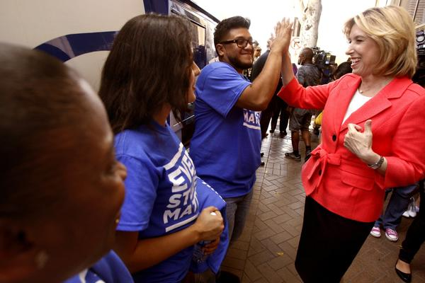 Los Angeles mayoral candidate Wendy Greuel, right, gets a high-five from Community Coalition member Jorge Hernandez after voicing her support of the proposal to make L.A. Unified the first school district in California to ban suspensions for willful defiance.