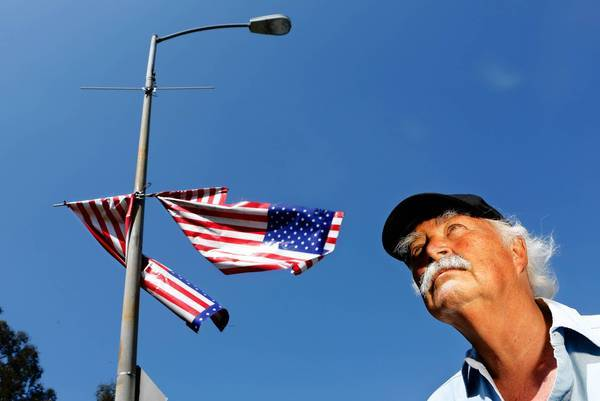 "Robert Rosebrock stands near battered American flags that were hung last year in West L.A. ""It was offensive and an insult to all who have defended the Flag, particularly to the patients at the VA hospital,"" he wrote in an opinion piece."