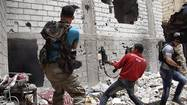Free Syrian Army fighters return fire after what they say was during clashes with forces loyal to President Bashar al-Assad in Deir al-Zor