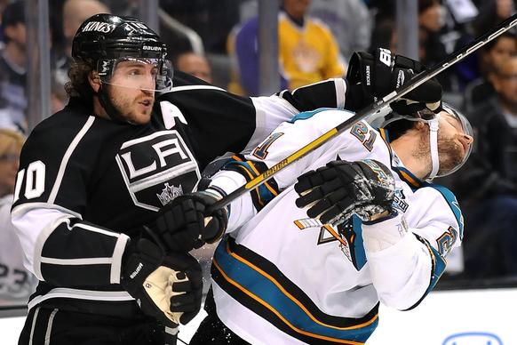 Kings' Mike Richards shoves San Jose Sharks' TJ Galiardi in the face after battling for the puck.