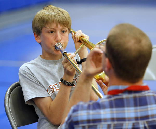 Abe Weiland, left, watches the instructions from Jeremy Schutter, back to camera right, as Weiland tried playing a trombone Tuesday at instument selection night for fifth-graders considering band next fall in middle school. photo by john davis taken 5/14/2013