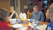 "Dave Thoen and his family say grace before dinner in Bloomington, Minn. Thoen received ""islet"" cells to treat his form of diabetes. At the table are his wife, Denise, and sons Reese, left, and Riley, right."