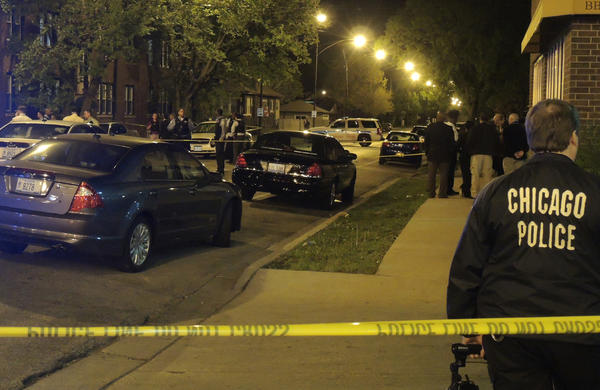 Chicago Police officers work at the scene where a man was shot by police around midnight. According to officials, the man was shot after pointing a gun at an officer in the 1600 block of East 83rd Street in Chicago.