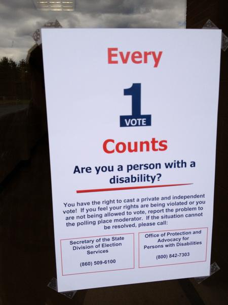 A sign saying every vote counts, and a notice for those with disabilities about their right to vote.