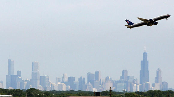 A United Airlines jet takes off with the Chicago skyline in background at O'Hare International airport, Thursday, July 14, 2011.