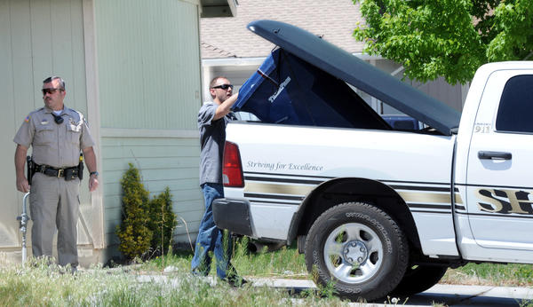 Investigators load a sealed garbage container into the back of a Lyon County sheriff's vehicle in Fernley, Nev. Five people were killed in the area Monday.