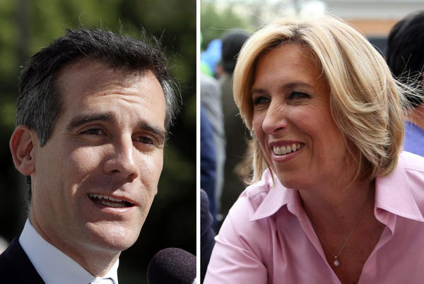 Los Angeles mayoral candidate Eric Garcetti speaking to media, left, and Wendy Greuel.