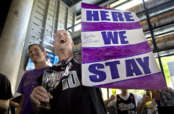 "Kings fan Kris Haskins holds a ""Here We Stay"" sign after hearing the NBA owners rejected the franchise's move to Seattle on Wednesday."