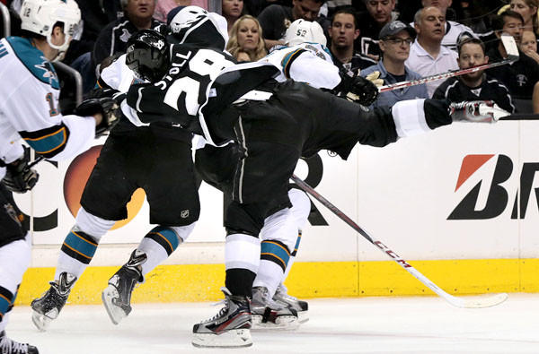 Kings center Jarret Stoll gets knocked off his skates from a hit by Sharks left wing Raffi Torres (hidden from view) in Game 1 of the Western Conference semifinals on Tuesday at Staples Center.