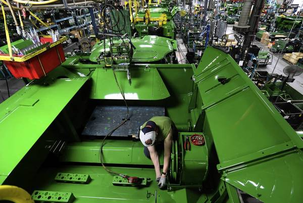 Deere employee Jeremy Ray works on the grain tank of a harvester Wednesday as the massive machine makes its way down the assembly line at the plant in East Moline, Ill.