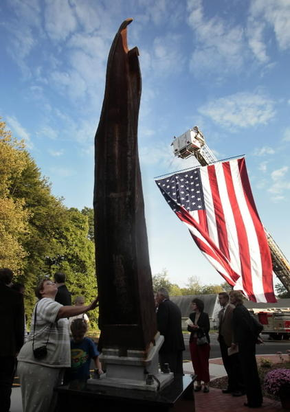 Corinne Nocida, lower left, touches a twisted steel girder salvaged from the wreckage of the World Trade Center south tower Thursday evening before dedication ceremonies opening the 9/11 Memorial Sports Center at the William J. Pitkin Community Center in Wethersfield.