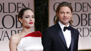 File photo of actors Angelina Jolie and Brad Pitt posing for photographers as they arrive at the 69th annual Golden Globe Awards in Beverly Hills