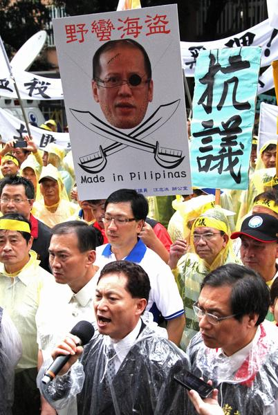 "Taiwanese fishermen hold a poster of Filipino President Benigno Aquino III with the label ""barbarian pirate"" during a protest against the shooting death of a fellow fisherman last week by the Filipino coast guard."