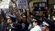 BEIJING -- Surrounded and pushed back by police, hundreds of people shouted and marched again in the southern China city of Kunming to protest the construction of a petrochemical plant.