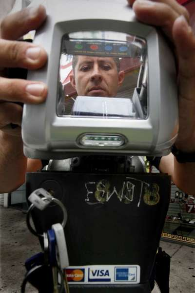 A technician reassembles a parking meter in Los Angeles that had been jammed with a wire and a gum wrapper by someone trying to beat payment in 2010. A state bill would prevent cities from ticketing drivers who park at broken meters.