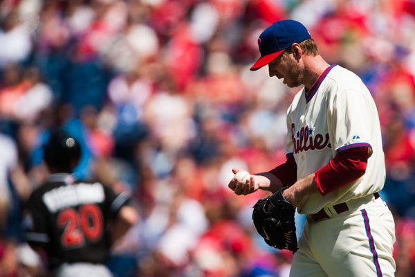 Philadelphia Phillies pitcher Roy Halladay (34) looks at the ball after hitting Miami Marlins center fielder Justin Ruggiano (20) with a pitch during the first inning at Citizens Bank Park.