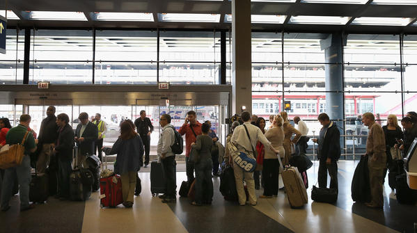 Passengers wait in line to reschedule flights at O'Hare Airport last month.