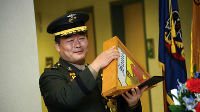 Lt. Col. Kang Moon Ho holds a Somerset County flag presented to him by Commissioners.