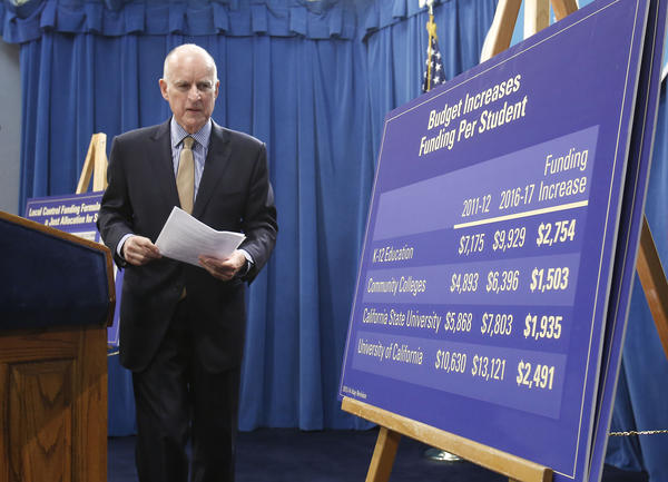 Gov. Jerry Brown walks past an education funding chart after presenting his revised 2013-14 state budget plan at the Capitol in Sacramento on Tuesday.