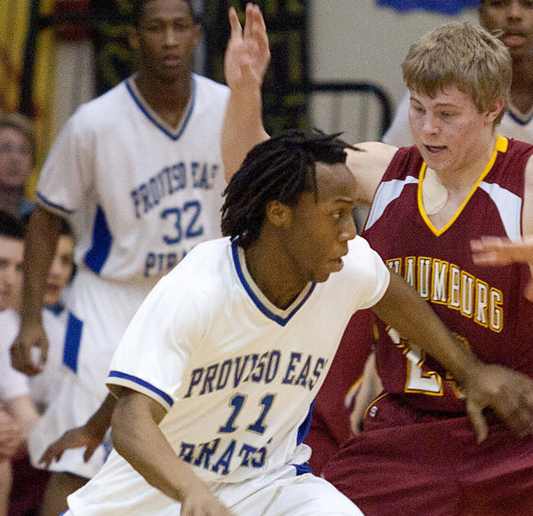 Deshamone McCarty (left) of Proviso East is guarded by Schaumburg's Kyle Bolger during a game March 9, 2012.